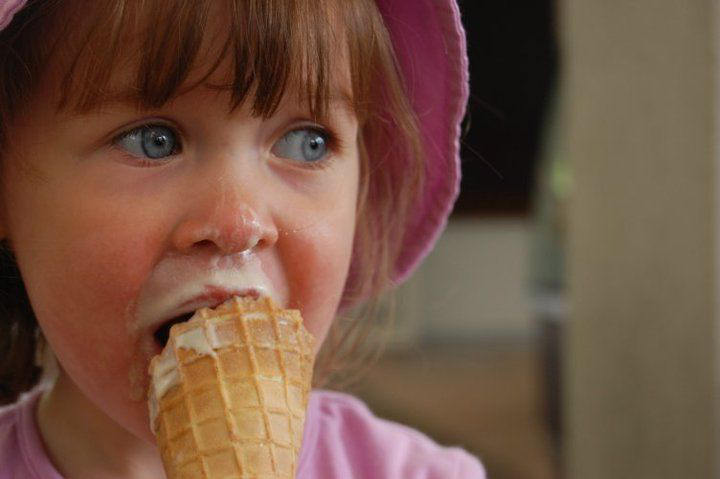 Pretty young girl in a pink hat enjoying a Rays Ice Cream cone